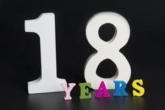 Buchstaben und Zahlen für achtzehn Jahre auf einem schwarzen Hintergrund Lizenzfreies Stockbild