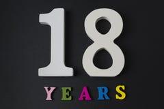 Buchstaben und Zahlen für achtzehn Jahre auf einem schwarzen Hintergrund Lizenzfreie Stockfotografie