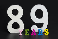Buchstaben und Zahlen neunundachzig Jahre alt auf einem schwarzen Hintergrund Lizenzfreies Stockbild