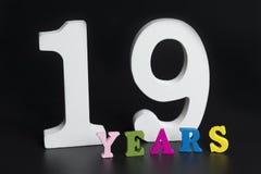 Buchstaben und Zahlen neunzehn Jahre alt auf einem schwarzen Hintergrund lizenzfreie stockfotos