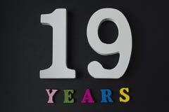 Buchstaben und Zahlen neunzehn Jahre alt auf einem schwarzen Hintergrund stockfotografie