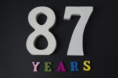 Buchstaben und Zahlen siebenundachzig Jahre alt auf einem schwarzen Hintergrund Lizenzfreie Stockfotografie