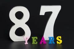 Buchstaben und Zahlen siebenundachzig Jahre alt auf einem schwarzen Hintergrund Lizenzfreies Stockfoto
