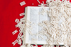 Buchstaben werden auf das Buch zerstreut lizenzfreies stockbild