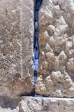 Buchstaben zum Gott geschoben zwischen den Steinen auf Klagemauer lizenzfreie stockbilder