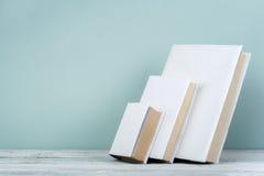 Buchstapel, gebundenes Buch reserviert auf Holztisch- und Blauhintergrund Zurück zu Schule Kopieren Sie Raum für Text getrennte a Stockfoto