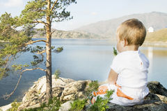 Buchtarma. Child seated on the shores of  Inlet. Royalty Free Stock Photo