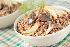 Buchweizenbrei mit gebratenen Pilzen und Zwiebeln Lizenzfreie Stockfotos