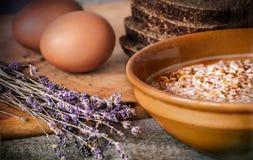 Buchweizenbrei mit Milch in einer Lehmplatte, im Roggenbrot auf einem Küchenbrett, in den Eiern und im trockenen Lavendel Landleb Stockfoto