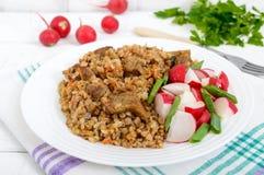 Buchweizenbrei mit Stücken Fleisch und Salat von Rettichen Lizenzfreies Stockbild