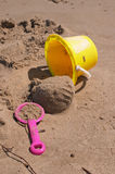 Buck and shovel on sand. Yellow buck and pink shovel on the beach sand Royalty Free Stock Photography