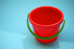 Bucket. Red bucket and a blue background Royalty Free Stock Photos