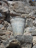Bucket in the ancient ruins. Dirty bucket. Stones in the background and the foreground Royalty Free Stock Image