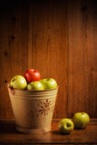 Bucket of Apples. Bucket of green and red apples on wooden background Royalty Free Stock Images