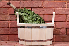 Bucket for a bath on a brick surface. Royalty Free Stock Photo