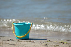 Bucket on beach. Bucket on the beach with a small wave out of focus in the background Royalty Free Stock Photos