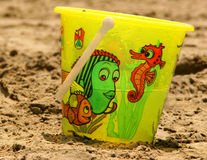 The Bucket On The Beach. A childs brightly coloured plastic bucket standing on the sand stock photo