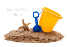 Bucket on beach with blue shovel and starfish Stock Photos