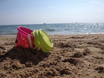 Bucket on a beach. Pink bucket with green sieve abandoned on Stock Photo
