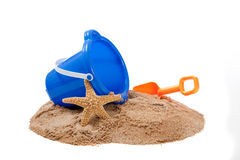 Bucket on a beach with a shovel and starfish Royalty Free Stock Photo