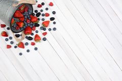 Bucket of Berries Spill. A bucket of berries spilling onto a rustic white kitchen table. High angle shot with the pail in the upper left corner leaving room for Royalty Free Stock Images