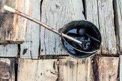 A bucket of black tar boils on the fire for use in repair and waterproofing. A bucket of black tar boils on the fire for use in repair and waterproofing stock image
