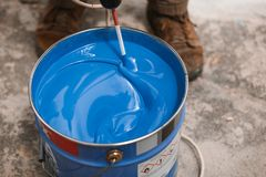 Bucket of blue paint mixing on motion stock photos