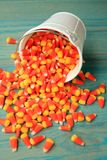 Bucket of candy corns spilled out on wooden floor Royalty Free Stock Photo