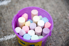 Bucket of chalk. Purple bucket of chalk sitting on a sidewalk Stock Photography