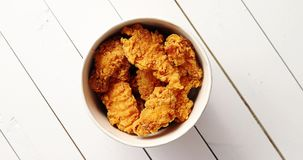 Bucket of chicken wings. From above shot of bucket full of tasty fried chicken wings standing on white lumber tabletop stock footage