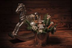 Bucket with christmas decorations near toy horse Stock Photo