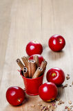 Bucket of cinnamon sticks on wooden table. Red apples around Royalty Free Stock Images
