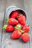 Bucket complètement des fraises se trouvant sur un fond en bois Images stock
