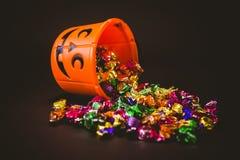 Bucket con los chocolates durante Halloween sobre fondo negro Fotografía de archivo
