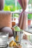 A bucket cup of pistachio ice cream topped with corn cones on white table in on the summer veranda. A bucket cup of pistachio ice cream topped with corn cones on royalty free stock photos