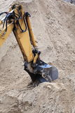 Bucket digger of an earthmover. On sand background Stock Photos
