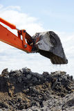 Bucket dropping clay and dirt. Bucket of orange mechanical digger dropping a scoop of clay soil on heap of dirt during major rural construction Royalty Free Stock Photo