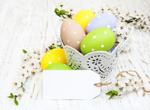 Bucket with easter eggs. Greeting card and cherries blossom on a old wooden background Stock Images