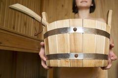 Bucket en las manos de las mujeres en sauna, accesorios del baño Fotos de archivo libres de regalías