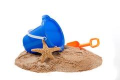 Bucket en una playa con una pala y una estrella de mar Foto de archivo libre de regalías