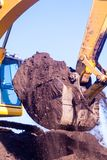 Bucket of an excavator against mountain and sky stock images