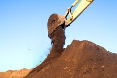 Bucket of an excavator against mountain and sky stock photos