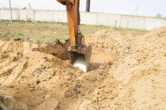 Bucket excavator digging a deep hole Stock Photo