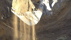 The bucket of the excavator digs the ground and carries it to another place.  stock video
