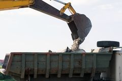 Bucket of an excavator pouring rock on the back of a truck on a sky background royalty free stock image