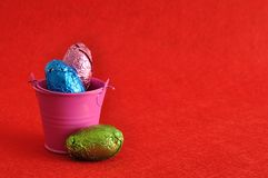 A bucket filled with easter eggs. On a red backgrounds Royalty Free Stock Photos
