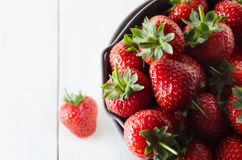 Bucket Filled with Strawberries on White Wood Planked Table. Overhead close up of a metal bucket, filled with red strawberries. One strawberry has fallen on Stock Image