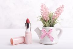 Bucket with flowers and lipstick. Artificial flowers and open lipstick. Perfect gift for any woman royalty free stock image