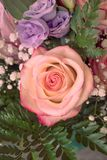 A bucket of flowers with pink and violet roses