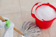 Bucket with foamy water and mopping the tile floor. Red bucket with foamy water and mopping the tile floor Royalty Free Stock Photos